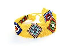 Färgrika vävde prydde med pärlor Zulu Wrist Band Bracelet på vit Royaltyfri Foto