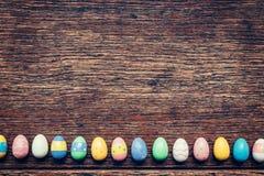 Färgrikt easter ägg på wood bakgrund med utrymme Grunt djup av sätter in Arkivfoto