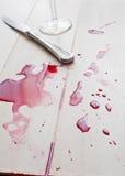 Färgstänk av den spillda rött vin och kniven Arkivfoto