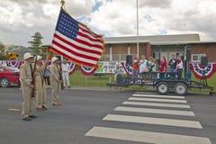 Färgvakten som leder fjärdedel av Juli, ståtar med en amerikanska flaggan, i Lima Montana Fotografering för Bildbyråer