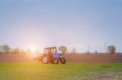 Früh an der Dämmerung auf Frühlingsmorgen beleuchtete ein Traktor durch die Strahlen der Sonne, Lizenzfreies Stockbild