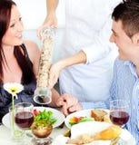 Fröhliche junge Paare, die an der Gaststätte speisen Lizenzfreies Stockfoto