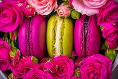 Frühlingsbeeren-Farbmakronen mit Rosenhintergrund mit Liebe Lizenzfreie Stockfotos