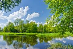 Frühlingslandschaft mit Fluss und Wolken auf dem blauen Himmel Stockbild