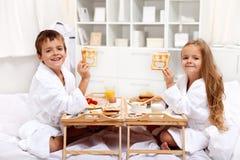 Frühstück im Bett mit glücklichen Kindern Lizenzfreies Stockfoto