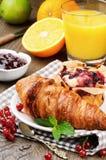 Frühstück mit Orangensaft und frischem Hörnchen Stockfotos