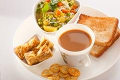 Frühstück - Tee, Poha mit Brot und Keks. Stockfotografie