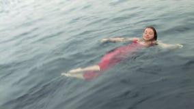 Fri dykaremodell i en röd klänning i vatten i Röda havet stock video