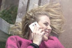 Fri glad kvinna som använder hennes mobiltelefon i en parkera på en solig dag royaltyfria foton