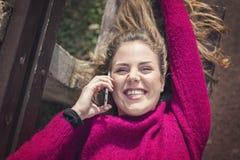 Fri glad kvinna som använder hennes mobiltelefon i en parkera på en solig dag royaltyfri foto
