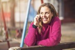 Fri glad kvinna som använder hennes mobiltelefon i en parkera på en solig dag fotografering för bildbyråer