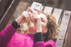 Fri glad kvinna som använder hennes mobiltelefon i en parkera på en solig dag royaltyfri bild