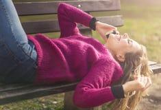 Fri glad kvinna som använder hennes mobiltelefon i en parkera på en solig dag arkivfoto