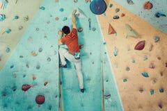 Fri klättrareman som klättrar den konstgjorda stenblocket Arkivbild