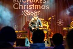 Fri konsert i stadens centrum Bucharest för spelmanVasile Seicaru Singing At Christmas marknad Arkivbilder