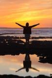 Fri kvinna som tycker om frihet på stranden på solnedgången Fotografering för Bildbyråer