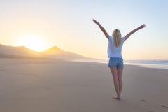 Fri kvinna som tycker om frihet på stranden på soluppgång Royaltyfri Fotografi
