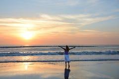 Fri kvinna som tycker om tid på stranden på soluppgång Arkivbilder