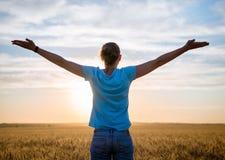 Fri lycklig kvinna som tycker om den utomhus- naturen och frihet Kvinna med armar som är utsträckta i ett vetefält i solnedgång Royaltyfri Bild