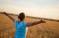 Fri lycklig kvinna som tycker om den utomhus- naturen och frihet Kvinna med armar som är utsträckta i ett vetefält i solnedgång Arkivbild