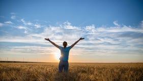 Fri lycklig kvinna som tycker om den utomhus- naturen och frihet Kvinna med armar som är utsträckta i ett vetefält i solnedgång Royaltyfria Bilder