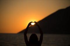 Fri lycklig kvinna som tycker om solnedgång Omfamna det guld- solskenglödet av solnedgången som tycker om fred, serenitet i natur Royaltyfri Foto