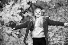 Fri och lycklig cutie Blont långt hår för barn som går i det utomhus- varma omslaget Flickan som är lycklig i rött lag, tycker om royaltyfria foton