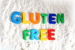 Fri text för gluten som ut stavas med kulöra bokstäver i vitt mjöl royaltyfri bild