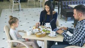 Fri-Time av den unga familjen i kafé Att bry sig modern frågar nyckfull liten dauhter att äta grönsaker Under tiden är fadern stock video