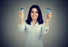 Fri ung kvinna för lycklig skuld som itu rymmer en kreditkort klippta stycken Arkivbild