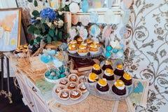 Friandise de vacances Petits gâteaux avec de la crème et des fruits et des bruits de gâteau bleu et blanc décorés des coeurs de p Photo libre de droits