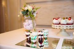 Friandise, une table avec des bonbons et desserts sur la table Secouez avec les petits gâteaux délicieux, bruits de gâteau, biscu photos stock