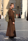 Friar to the square of the Vatican. A friar is the square of the Vatican (Rome - Italy) / Bring habit and a backpack slung / is watching with a slight smile as royalty free stock photography