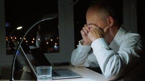 A fricção executiva do homem de negócios eyes quando trabalho duro pelo caderno no escritório da noite vídeos de arquivo