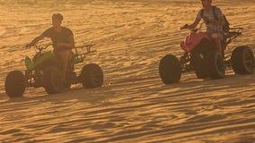 Fricción de la arena del funcionamiento de los patios del primer que compite con en las dunas blancas en la puesta del sol metrajes