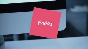 Friday. Days of the week. The inscription on the sticker on the monitor. Message. Motivation. Reminder. Handwritten text written with a marker. Color sticker stock footage