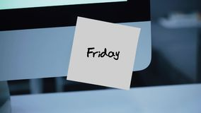 Friday. Days of the week. The inscription on the sticker on the monitor. Message. Motivation. Reminder. Handwritten text written with a marker. Color sticker stock video