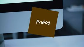 Friday. Days of the week. The inscription on the sticker on the monitor. Message. Motivation. Reminder. Handwritten text written with a marker. Color sticker stock video footage