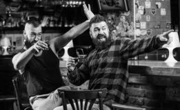 Friday relax in pub. Cheers concept. Hipster brutal bearded man drinking alcohol with friend at bar counter. Men drunk. Friday relax in pub. Cheers concept royalty free stock photo