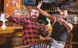 Friday relax in pub. Cheers concept. Hipster brutal bearded man drinking alcohol with friend at bar counter. Men drunk royalty free stock image
