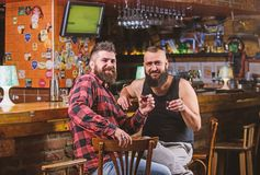 Friday relax in pub. Friends relaxing in pub. Cheers concept. Hipster brutal bearded man drinking alcohol with friend at. Friday relax in pub. Friends relaxing stock photos