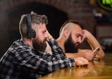 Friday relaxation in bar. Hipster bearded man spend leisure at bar counter. Order drinks at bar counter. Men with royalty free stock photo