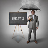 Friday 13 text on blackboard with businessman Royalty Free Stock Photos