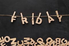 Friday word made of wooden letters. Word Friday spelled with wooden letters on black background. Characters handing on clothespins, top view, copy space Stock Image