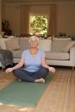 Fridfull hög kvinna som hemma mediterar i lotusblommapositionen Arkivbild