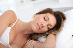 Fridfull kvinna som sover i säng Fotografering för Bildbyråer