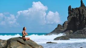 Fridfull meditationyoga Turist- kvinna för brunett som mediterar i lotusblommaposition på udden ovanför scenisk Praia da Marinha stock video