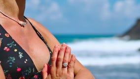 Fridfull meditationyoga Turist- kvinna för brunett som mediterar i lotusblommaposition på udden ovanför scenisk Praia da Marinha arkivfilmer