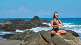 Fridfull meditationyoga Turist- kvinna för brunett som mediterar i lotusblommaposition på udden ovanför scenisk Praia da Marinha lager videofilmer