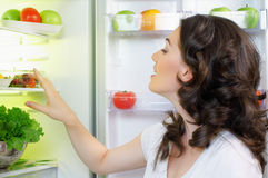 Fridge with food. A hungry girl opens the fridge Royalty Free Stock Image
